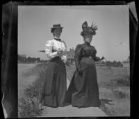 Minnie Kellum and Lucretia Kellum stand on a sidewalk in their neighborhood, Los Angeles, about 1899
