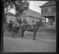 H. H. Cooper in a carriage parked in front of the West's home at 240 South Griffin Avenue, Los Angeles, (circa 1901?)