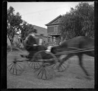H. H. Cooper drives by the West's house in a horse-drawn carriage, Los Angeles, (circa 1901?)