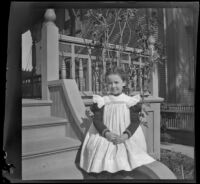 Josephine Lacy sits on the front porch steps of the Lacy family home, Los Angeles, about 1900
