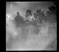 Agnes Hawley stands holding a fan in the Whitaker's front yard, Los Angeles, about 1898
