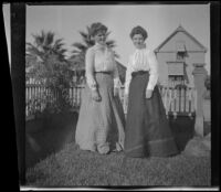 Agnes Hawley and Mertie Whitaker stand in the Whitaker's front yard, Los Angeles, about 1898