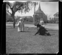 Daugherty brothers play with Guy West's dog, Los Angeles, 1897