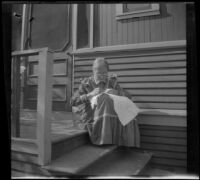 Wilhelmina West sews while sitting on the back porch of the West's house, Los Angeles, about 1899