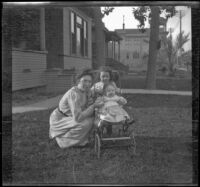 Mary West poses on a front lawn with her daughters, Elizabeth and Frances, Los Angeles, about 1907