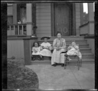 Mary West sits on the front steps of a house with her daughters, Elizabeth and Frances, as well as another girl, Los Angeles, about 1907
