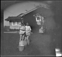Elizabeth and Frances West stand in a washboiler in the backyard of the West's house, Los Angeles, about 1914