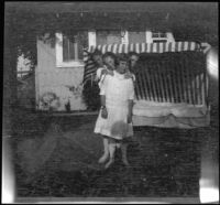 Elizabeth and Frances West pose in the backyard of the West's home with their cousin, Frances Cline and unknown boy, Los Angeles, about 1914
