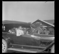 Mary West sits in H. H. West's Mitchell car, which is parked in front of their house, Los Anglees, about 1916