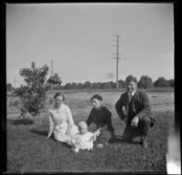 Gertrude Teel, Hattie Cline, John Teel and baby Ambrose Cline sit in the grass at John Teel's ranch, Los Angeles, [about 1915]