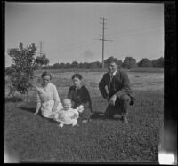 Gertrude Teel, Hattie Cline, John Teel and baby Ambrose Cline sit in a field at John Teel's ranch, Los Angeles, [about 1915]