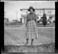 Lois Winkler stands on a curb and poses in front of her family's home, Los Angeles, about 1918