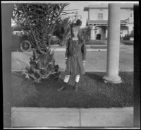 Tacoma Winkler stands on a tree lawn and poses in front of her family's home, Los Angeles, about 1918