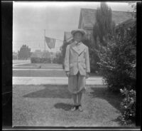H. H. West Jr. stands in front of a house wearing a suit, Los Angeles, about 1925