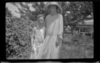 Mertie West stands in a backyard with her arm around H. H. West Jr., Los Angeles, about 1925