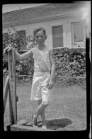 H. H. West Jr. leans on a wooden post in a backyard, Los Angeles, about 1925
