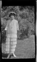 Mertie West stands in front of bushes, Monterey, 1924