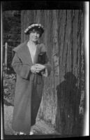 Mertie West stands next to a redwood tree in Big Basin Redwoods State Park, Boulder Creek vicinity, 1924