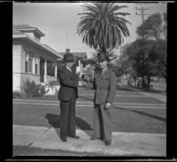 H. H. West and Gilbert Cecil West shake hands while standing on H. H. West's front walk, Los Angeles, 1941