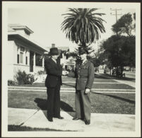 H. H. West and Gilbert Cecil West shake hands while standing on H. H. West's front walk [photo, recto], Los Angeles, 1941