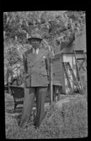 H. H. West stands in front of a wisteria plant in his backyard, Los Angeles, 1942
