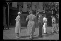 Mertie, Myrtle, and Evert West look at the footprints in the cement in front of Grauman's Chinese Theatre, Los Angeles, 1941