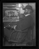 Frank E. Prior sitting at his desk at the Arcade depot (negative), Los Angeles, about 1900