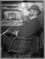 Frank E. Prior sitting at his desk at the Arcade depot (glass positive), Los Angeles, about 1900