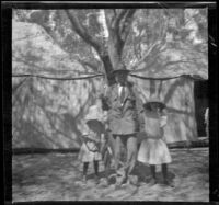 Frances West, H. H. West and Elizabeth West pose in front of a cluster of tents, Santa Catalina Island, about 1910