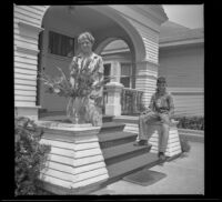 Mertie West stands next to a vase of flowers while Richard Siemsen sits on the porch behind her, Los Angeles, 1943