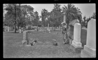 Mertie West stands by the decorated graves of Mr. and Mrs. George Miller West in Evergreen Cemetery on Decoration Day, Los Angeles, 1943