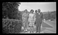 Elizabeth Siemsen, Dorothea Siemsen and H. H. West pose on a sidewalk in front of the Siemsen's residence, Glendale, 1943