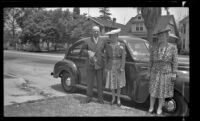 H. H. West, Mertie West and Josie Shaw pose near a car parked in front of H. H. West's residence, Los Angeles, 1943