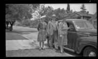 Mertie West, Will H. Shaw and Josie Shaw pose beside a car parked in front of H. H. West's residence, Los Angeles, 1943