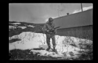 Fellow serviceman of H. H. West, Jr. poses with a rifle outside the barracks, Dutch Harbor, 1943
