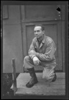 H. H. West, Jr. kneels and poses in front of his barracks at Fort Mears (negative), Dutch Harbor, 1942