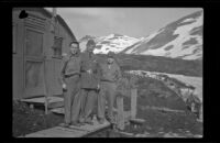 Three servicemen stand on the wood slat walkway outside the barracks, Dutch Harbor, 1943