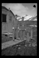 Two uniformed servicemen pose on the walkway in front of their quarters, Dutch Harbor, 1943
