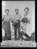 Agnes Hawley, John Ramboz and 2 other women pose while eating on the beach, Santa Catalina Island, about 1900