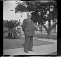J. E. Smith stands on the front walkway outside his home, Los Angeles, 1943