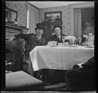 H. H. West and Dr. Bim Smith sit at the West's dining table during a birthday dinner, Los Angeles, 1944