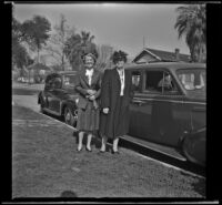 Mertie West and Josie Shaw stand next to a car parked outside the West's residence, Los Angeles, 1944