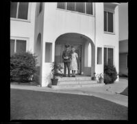 H. H. West, Jr. and Mertie West pose on the front porch of the West's new residence, Los Angeles, 1944