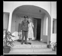 H. H. West, Jr. and Mertie West posing on the front porch of the West's new residence, Los Angeles, 1944