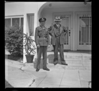 P.F.C. H. H. West, Jr. and H. H. West stand on the front steps of H. H. West's new residence, Los Angeles, 1944