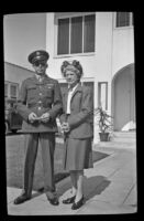H. H. West, Jr. and Mertie West stand on the sidewalk in front of the West's residence, Los Angeles, 1944