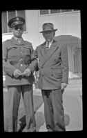 H. H. West, Jr. and H. H. West pose on the sidewalk in front of the West's residence, Los Angeles, 1944