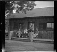 Maud West, Wayne West, Agnes Whitaker and Mertie West sit outside their cabin at Knight's Camp, Big Bear Lake, 1944