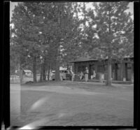 Distant view of Maud West, Agnes Whitaker and Mertie West sitting outside their cabin at Knight's Camp, Big Bear Lake, 1944