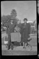 Wayne West and Maud West stand on the walkway in front of H. H. West's home and pose with their luggage, Los Angeles, 1944